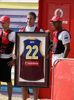 Luke Power from the Brisbane Lions presents Lewis Hamilton with a Brisbane Lions jersey