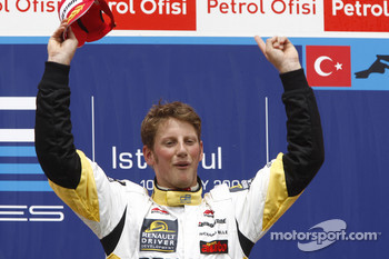 Romain Grosjean celebrates victory on the podium