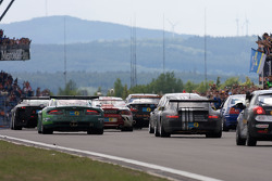 A group of cars parade on the front stretch