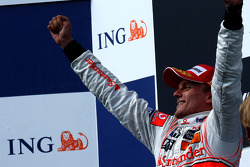 Podium: race winner Heikki Kovalainen celebrates