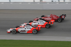 Helio Castroneves, Ryan Briscoe, and Dan Wheldon run three wide
