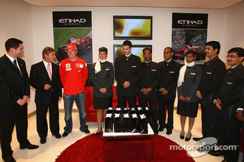 Kimi Raikkonen of Ferrari poses with Etihad staff at the opening of the Etihad Holiday Store at Marina Mall