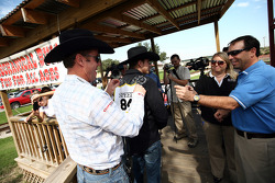 Former four-time bull riding champion Tuff Hedeman (left) helps NASCAR Sprint Cup Series driver Scott Speed with his No. 84 rodeo back number (which included a yellow rookie stripe) before the racer took a ride on a mechanical bull in the Fort Worth Stock