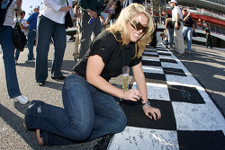 A cute fan writes messages on the start-finish line