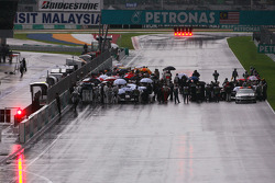 A starting grid is reformed while the rain keeps falling