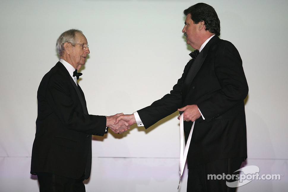 The first championship-winning car owner in NASCAR Sprint Cup Series history, Raymond Parks, receives his International Motorsports Hall of Fame medal from NASCAR President Mike Helton