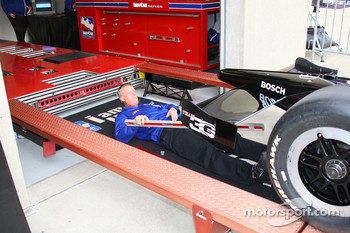 An Indy Racing League official is about to check the bottom of a car during tech inspection