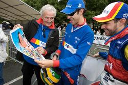 Hugues de Chaunac, Bruno Senna and Tiago Monteiro look at a cartoon