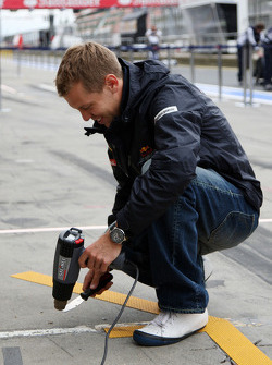 Sebastian Vettel, Red Bull Racing helps out by removing tape from his pit