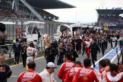 Red Bull Racing team run to watch the podium