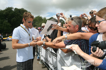 Jenson Button signs autographs for fans