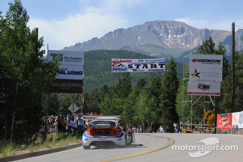 Andreas Eriksson takes a flying start over the start line on his way to Pikes Peak looming in the background