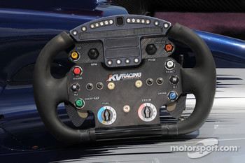 KV Racing Technology steering wheel up close, notice the green push to pass button on the bottom left