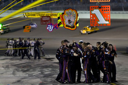 The No. 11 FedEx Toyota crew celebrates their win of the Ford 400 while the No. 48 Lowe's Chevrolet crew celebrate the NASCAR Cup Series Championship in the background