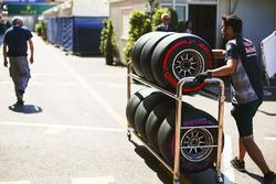 Un miembro del equipo Red Bull Racing transporta neumáticos en el paddock