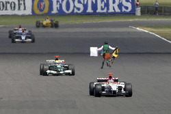 A man runs in front of the cars on track