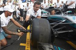 Lewis Hamilton, Mercedes AMG F1, tries his hand with a wheelgun on the car of his team mate