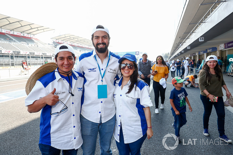 Fans pose for a photo in the pitlane,