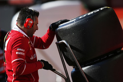 A Ferrari team member pushes a stack of tyres