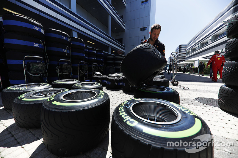 A Red Bull team member works on Pirelli tyres in the paddock