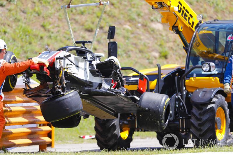 El coche dañado de Romain Grosjean Haas F1 Team VF-18 es retirado del circuito