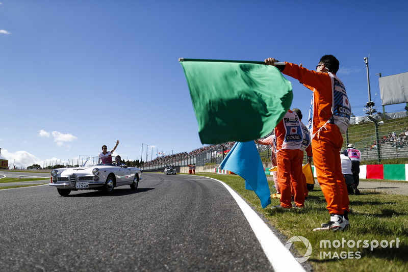Marshals wave flags as Charles Leclerc, Sauber, passes in the drivers parade