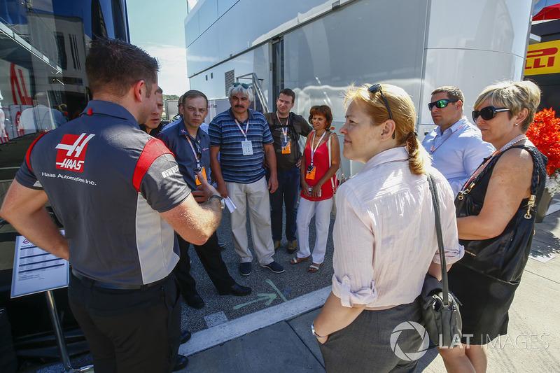 Un miembro del equipo Haas F1 Team da un recorrido a un grupo de invitados