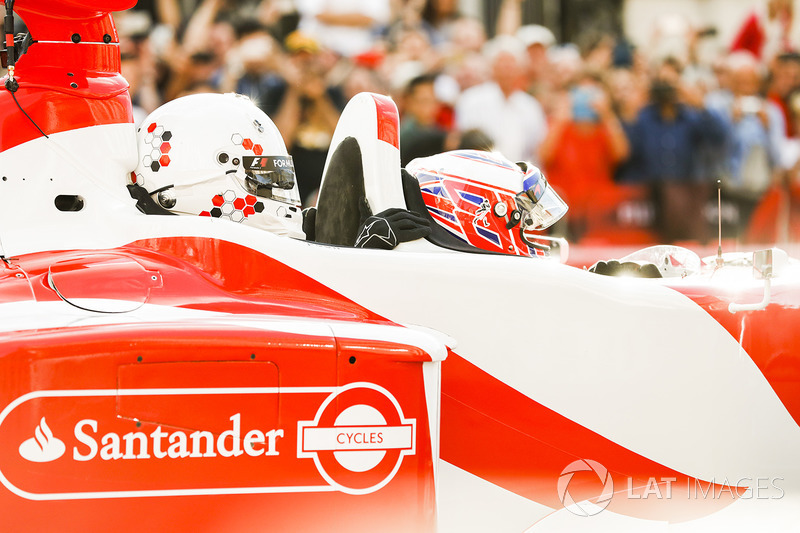 Jenson Button, McLaren, gives a passenger ride to Naomi Campbell in the 2 seater
