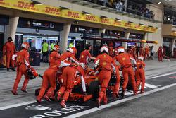 Механики Ferrari катят автомобиль SF71H Кими Райкконена в гараж