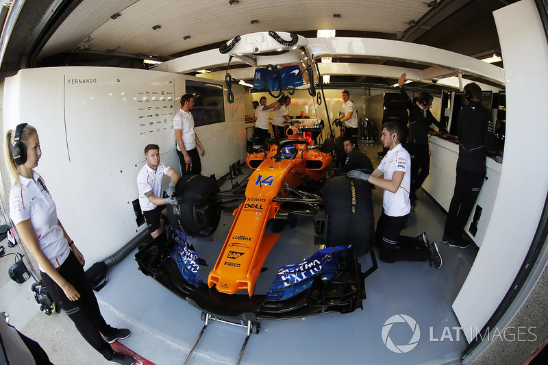 Fernando Alonso, McLaren MCL33, is attended to by mechanics in his pit garage