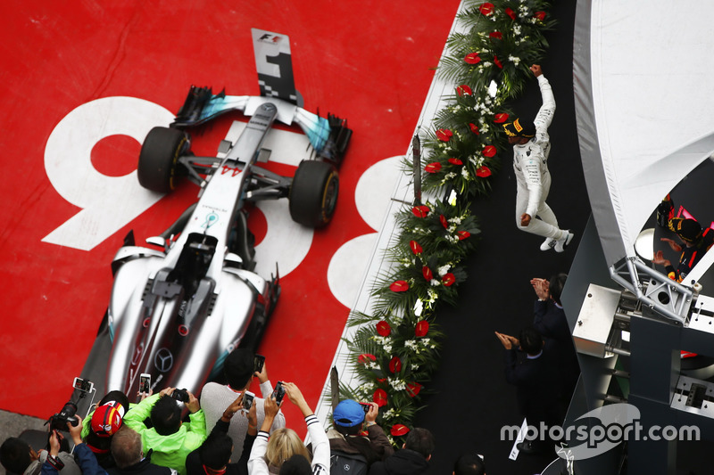 Lewis Hamilton, Mercedes AMG, celebrates victory on the podium with Max Verstappen, Red Bull Racing