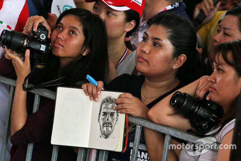A fan with a sketch drawing of Sebastian Vettel, Ferrari