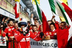 Гонщик Ferrari Себастьян Феттель празднует победу вместе с командой