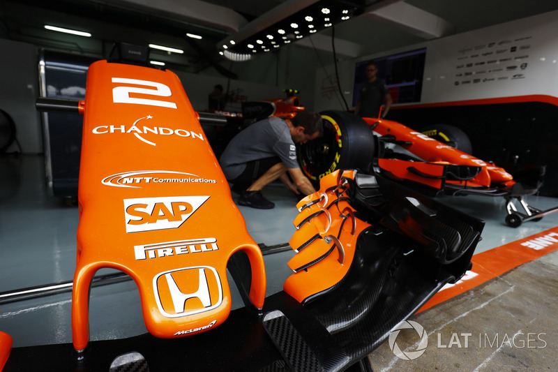 A McLaren nose cone, while a mechanic works on the Stoffel Vandoorne McLaren MCL32.