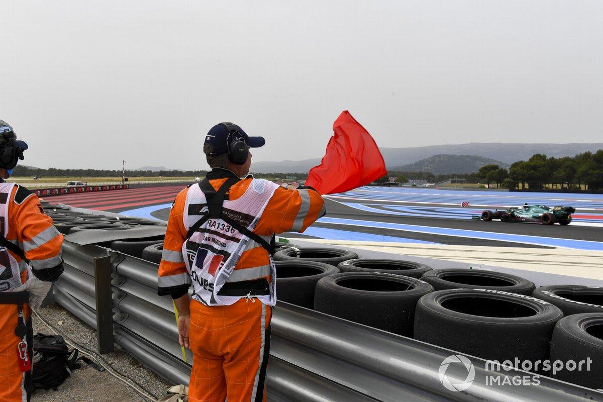 A marshal waves a red flag as Sebastian Vettel, Aston Martin AMR21, passes