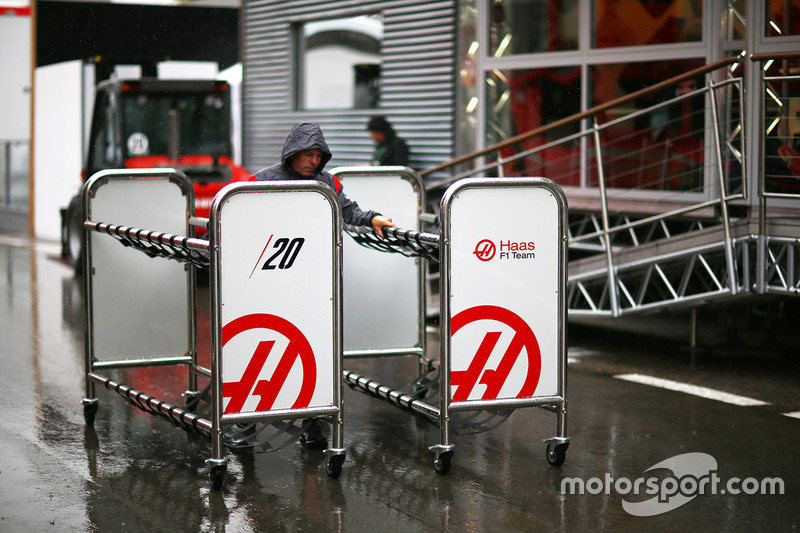 Haas F1 Team team members prepare equipment in a wet paddock