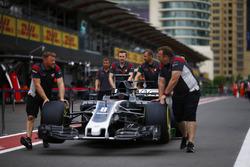 Haas F1 Team team members push the Romain Grosjean Haas F1 Team VF-17 along the pit lane