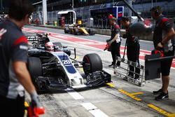 Kevin Magnussen, Haas F1 Team VF-17, stops in his pit garage as Nico Hulkenberg, Renault Sport F1 Te