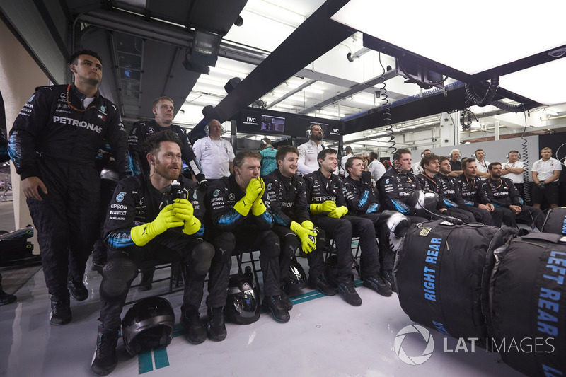 The Mercedes pit crew watch anxiously in the closing stages of the race