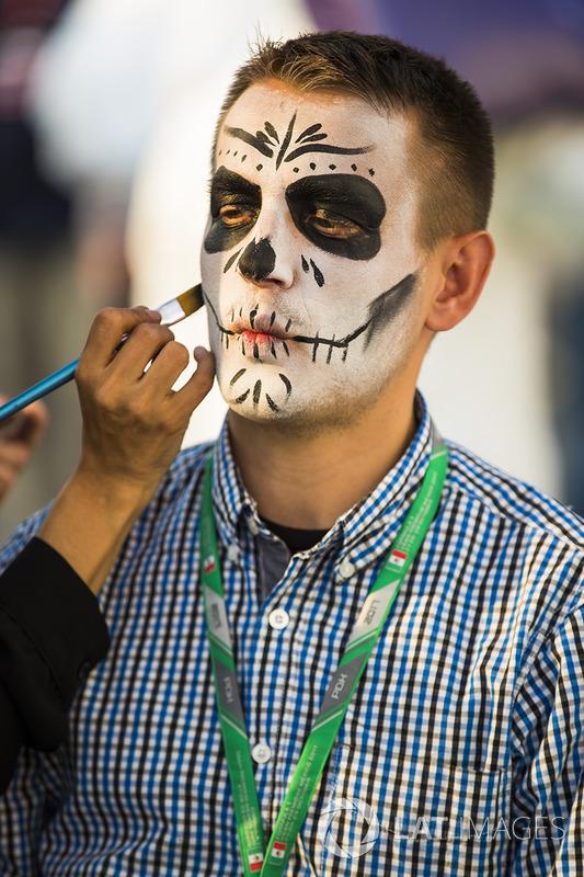 Caras pintadas del día de muertos a personas en el paddock