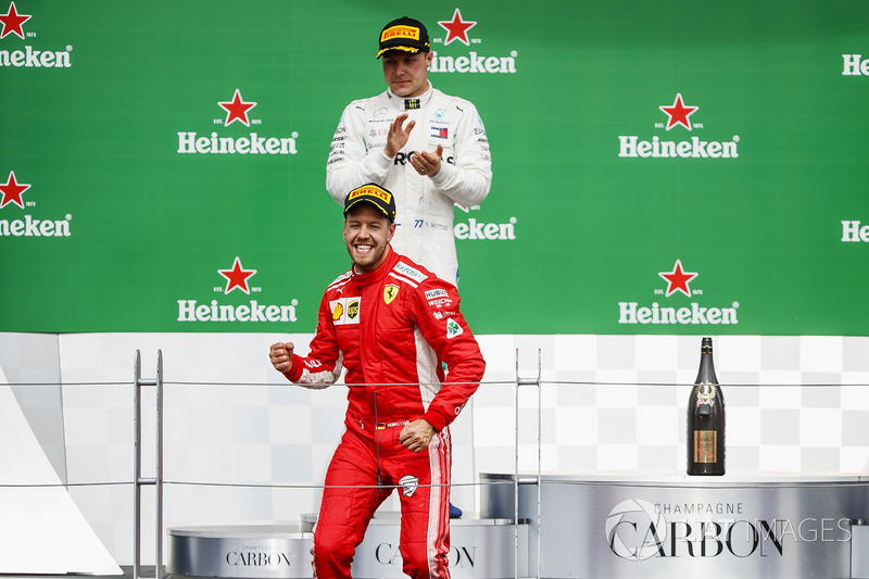 Sebastian Vettel, Ferrari, 1st position, celebrates victory on the podium as Valtteri Bottas, Merced