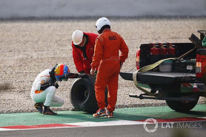 Fernando Alonso, McLaren, inspects the wheel