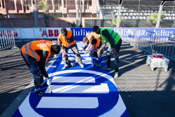 Track workers paint, Allianz logo on to the track