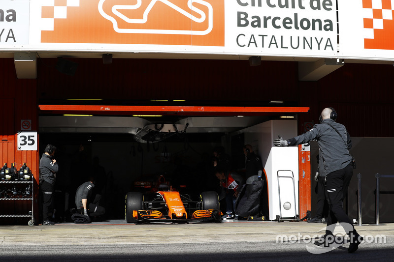 The McLaren garage door is raised as Fernando Alonso, McLaren MCL32 enters the pit lane