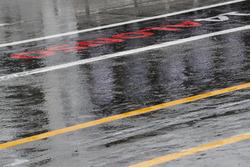 Rain pours down in the pit lane