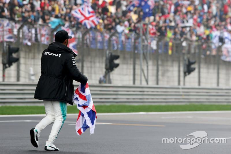 Lewis Hamilton, Mercedes AMG, toma la pista para entretener a los fans y recoge una bandera de la Unión