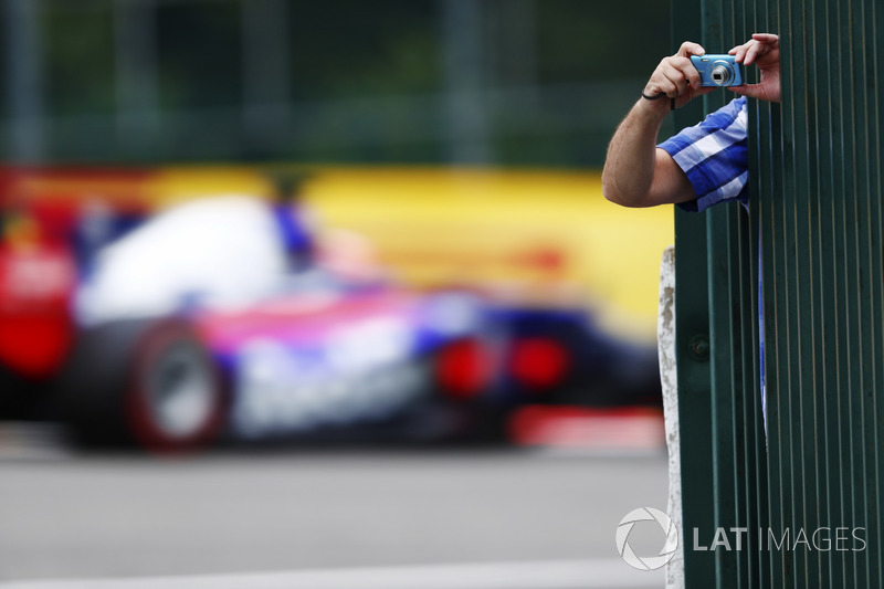A fan leans out to take some photos as Daniil Kvyat, Scuderia Toro Rosso STR12, passes through the background