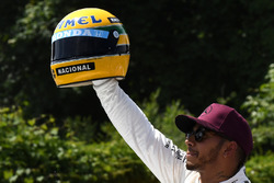 Pole sitter Lewis Hamilton, Mercedes AMG F1 celebrates in parc ferme, the helmet of Ayrton Senna