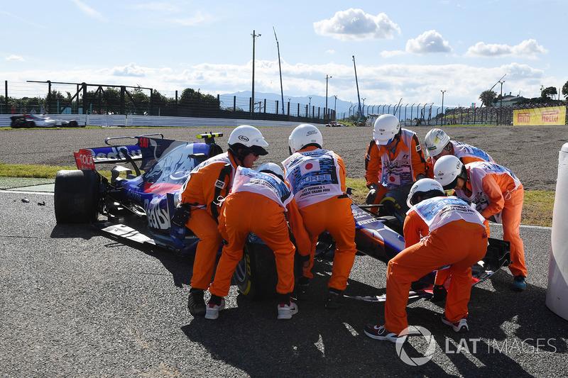 Oficiales de pista retiran el coche de Carlos Sainz Jr., Scuderia Toro Rosso STR12