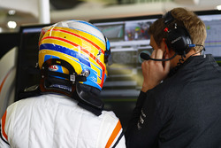 Fernando Alonso, McLaren, talks with his engineer in the garage
